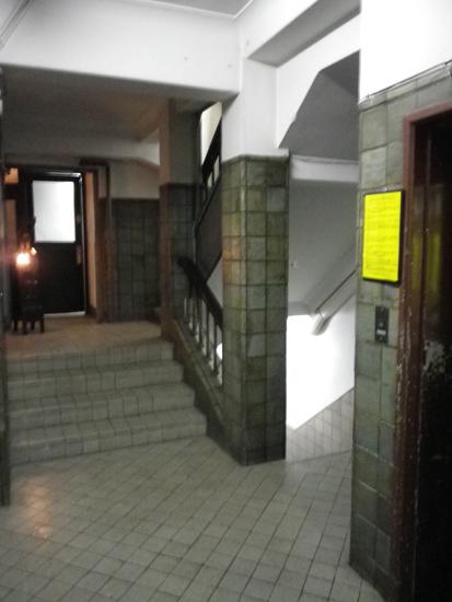 エントランスから奥の階段を臨む。右にはエレベーターが。